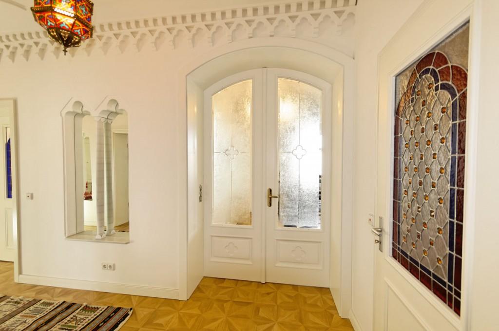 Zweiflügelige Segmentbogentür mit tiefer Zarge, Kassetten und Ornamentverglasung