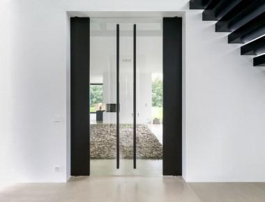 Elegante schwarze Pendel-Drehtür raumhoch mit viel Glas